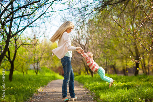 mother playing with child  in spring sunny day