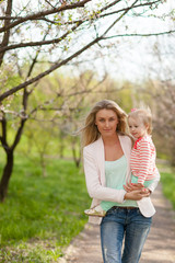 mother and daughter walking in spring garden