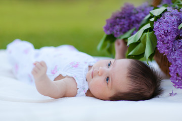 Baby girl lying in park with lilac bouquet in basket