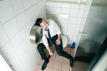Young sleeping drunk man on the toilette