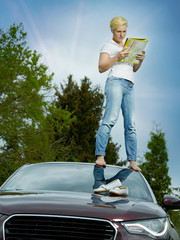 Beautiful woman on top of her car in field looking at map