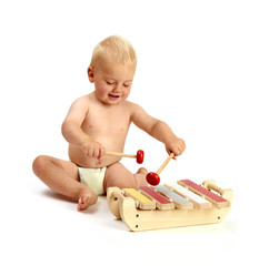 cute baby boy playing a xylophone musical instrument isolated on