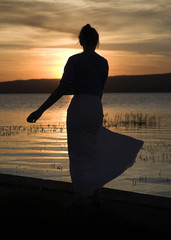Woman silhouette next to the lake, sunset