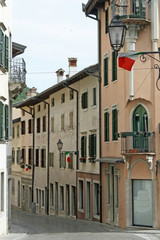 narrow country road in Friuli Gemona with Italian flags