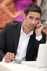 businessman with laptop on the phone having coffe