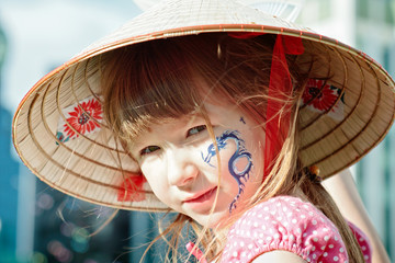 Portrait of a little girl in hat with blue dragon on her cheek