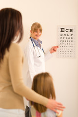 Pediatrician ophthalmologist point eye-chart