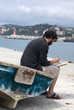 Painter painting a picture sitting on old row boat