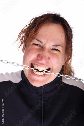 Young woman with open mouth biting a chain