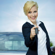 Pretty blonde woman proudly presents the key of her car