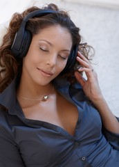 Beautiful woman enjoying music eyes closed
