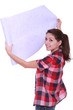 Young woman unrolling wallpaper
