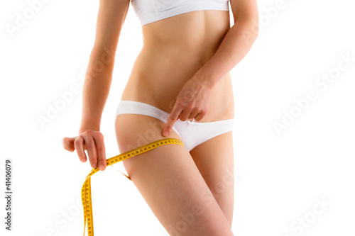 Woman measuring her slim body isolated on white