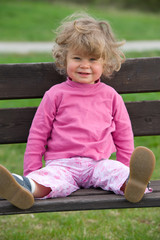 girl is sitteing on a park bench