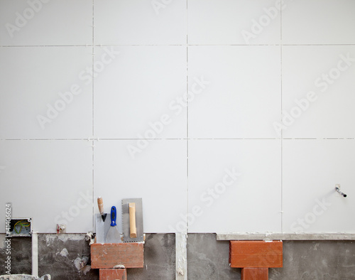 Poster tiles white wall contruction with trowels tools