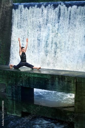 man doing the splits on  footbridge at the waterfall