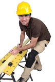 Tradesman using a plane to smooth a plank of wood