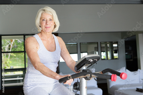 Mature woman using an exercise bike at home