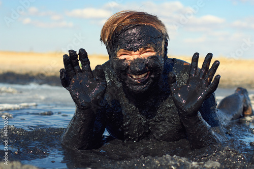 happy senior man lying in healing clay. outdoor