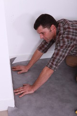 Profile view of man fitting carpet