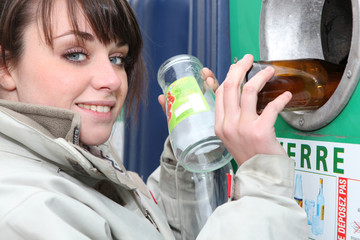 Woman recycling glass bottles