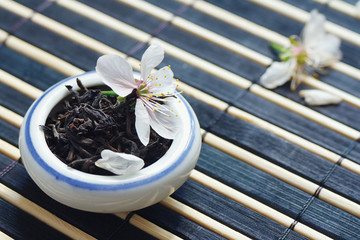 Jar of tea leaves and cherry blossoms on bamboo table