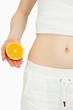 Close up of a woman placing an orange near her belly