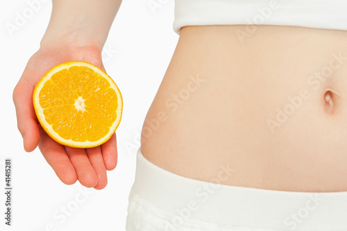 Woman placing an orange near her belly