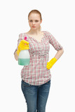Serious woman holding a spray bottle while standing