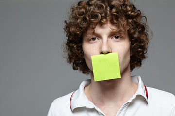Young man with a piece of paper covering his mouth