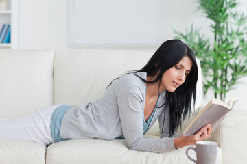 Woman lying on a sofa while reading a book