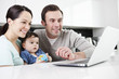 A couple and their baby son looking at a laptop