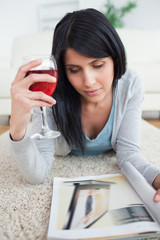Woman holding a glass of red wine while laying on the floor