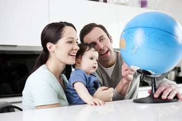 A couple and their baby son looking at a globe