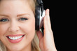 Smiling blonde woman listening to music through headphones