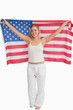 Cheerful blonde woman raising the American flag