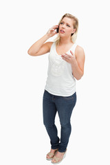 Serious blonde woman having a conversation on the phone