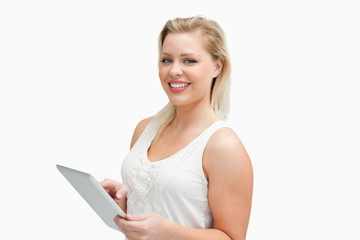 Cheerful blonde woman holding her tablet computer
