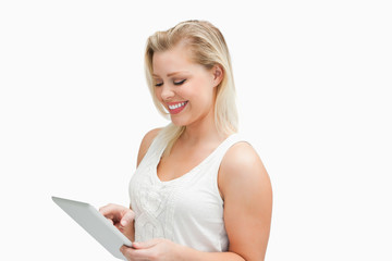 Smiling blonde woman using her tablet computer