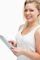 Cheerful blonde woman touching her tablet computer