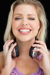 Happy blonde woman proudly holding her headphones
