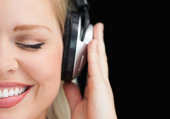 Joyful woman closing her eyes while listening to music