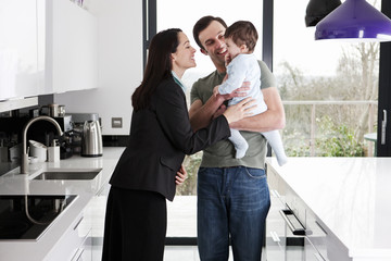 A working mother greeting her partner and baby son
