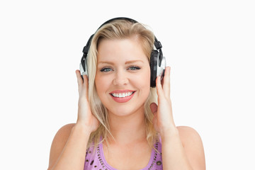 Smiling blonde woman placing her hands on her headphones