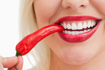 Happy woman eating a red chili