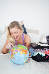 Student with a suitcase pointing on a globe
