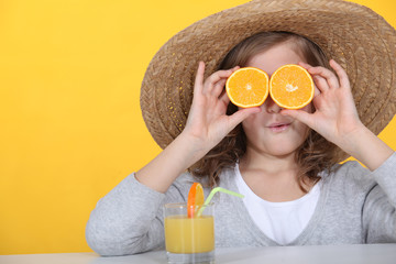 little girl hiding her eyes with slices of orange