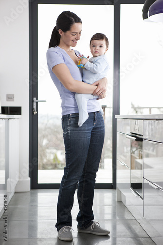 A mother standing in a kitchen holding her baby son
