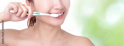 woman brushing teeth with green background