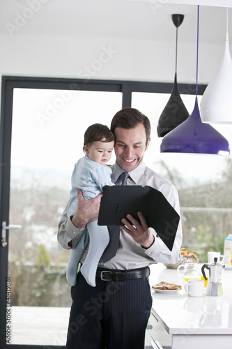 A father and baby son looking at a digital tablet